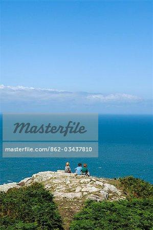 Au Royaume-Uni, pays de Galles, Pembrokeshire. Trois garçons assis surplombant Fishguard Bay et la mer d'Irlande le Pembrokeshire du sentier côtier sur la tête de Dinas.