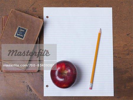 Nature morte d'Apple, papier, crayon et livres sur le Bureau