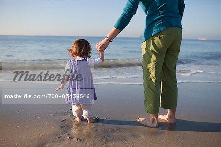 Hintere Ansicht der Mutter an Young Tochter Hand, stehend auf Beach, Long Beach, Kalifornien, USA