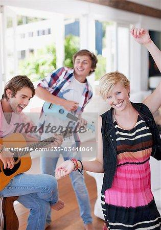 Hommes jouant de la guitare et ukulélé avec femme dansant