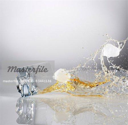 Verschütten von sinkenden Highball Glas Alkohol und Eis-Würfel