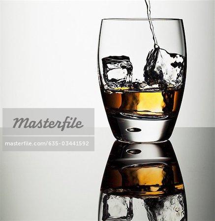 Alkohol in Highball-Glas mit Eiswürfeln Gießen