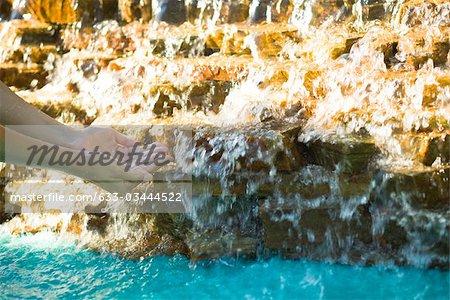 Attraper l'eau qui coule sur les rochers avec les mains