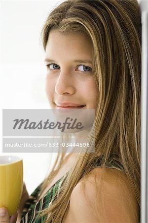 Jeune femme avec une tasse de café, portrait