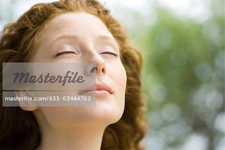 Junge Frau mit Augen geschlossen und heitere Ausdruck auf dem Gesicht, Porträt
