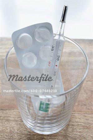 Pilules et thermomètre en verre