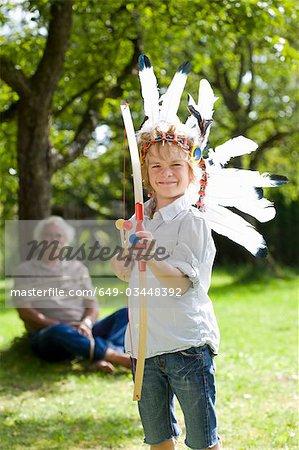 Garçon déguisé avec jouet arc et des flèches