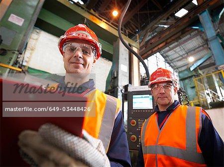 Ingénieurs en acier en usine avec le presse-papier