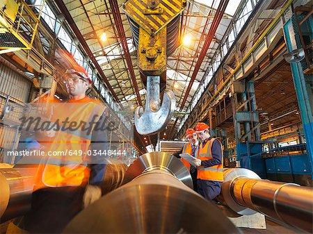 Ingénieurs avec des rouleaux d'acier fini