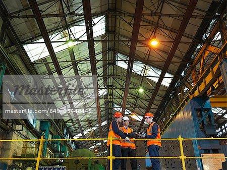 Steel Workers And Engineer In Factory