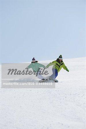 Mann und Frau Snowboarden Holding Hände