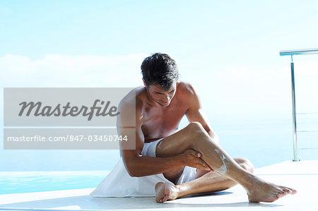 Landscape of handsome man sunbathing by pool.