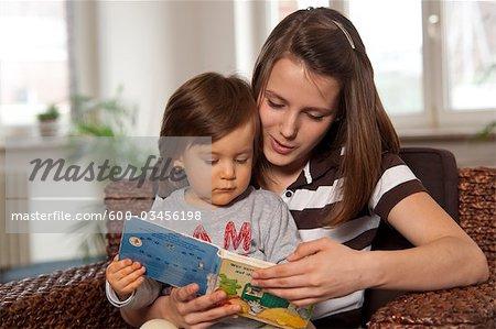 Teenage Girl Reading Book to Little Boy, Mannheim, Baden-Wurttemberg, Germany