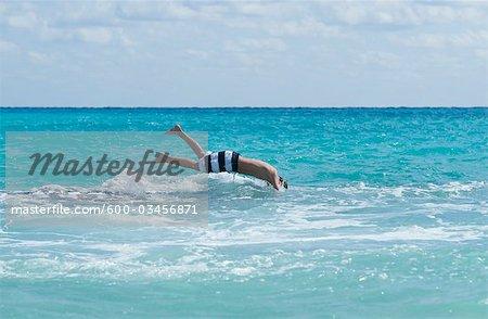Garçon plongeant dans l'eau, Playa del Carmen, péninsule du Yucatan, Mexique