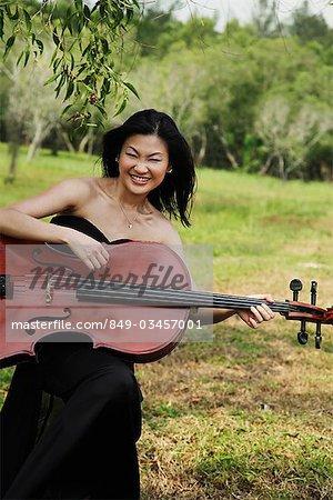 Femme jouant violoncelle comme une guitare et riant