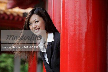 Jeune femme à la recherche de piliers rouges souriant