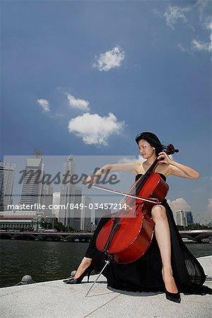 Chinesische Frau spielt Violoncello außerhalb vor Gebäuden