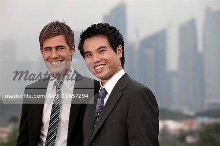 Chinese man et caucasienne homme debout en face de bâtiments