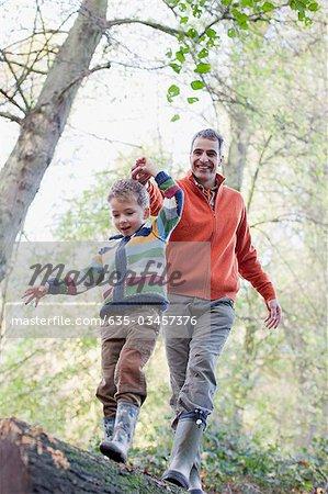 Père aidant les fils traversent le journal à l'extérieur