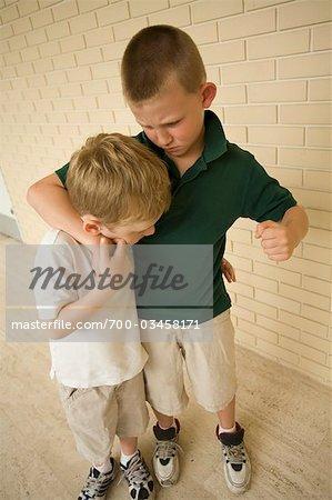 Big Boy Bullying Little Boy in School Corridor