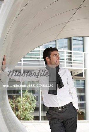 Businessman standing in modern archway, three quarter length