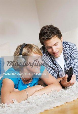 Adolescent couple couché sur le tapis et écouter de la musique, faible angle de vue
