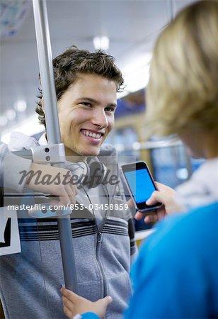 Jeune homme flirter avec la jeune fille dans la région métropolitaine, incliné la vue