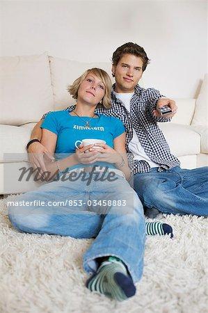Séance de couple adolescent en face du canapé et regarder la télévision, bas-angle de vue