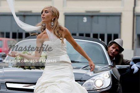 Mariée devant une voiture, marié en arrière-plan