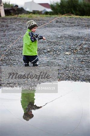 Petit garçon jouant avec pêche Pole, Grundarfjordur, péninsule de Snaefellsnes, Islande