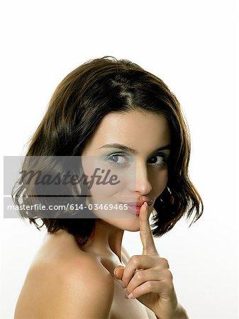 Jeune femme avec le doigt sur les lèvres