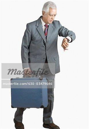 Geschäftsmann, tragen einen Koffer und Überprüfung der Zeit