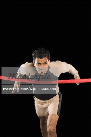 Athlète en cours d'exécution à travers une ligne de finition