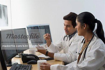 Femme médecin avec un médecin de sexe masculin examine un rapport de rayons x