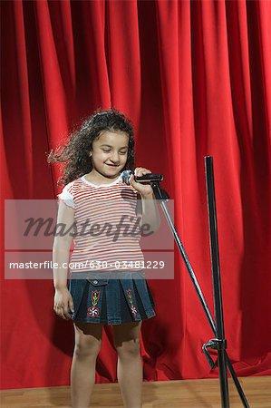 Mädchen auf einer Bühne mit einem Mikrofon durchführen