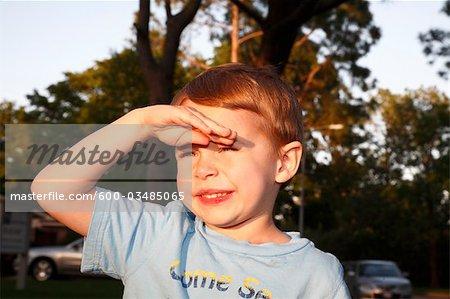 Gros plan du garçon en estompant les yeux du soleil