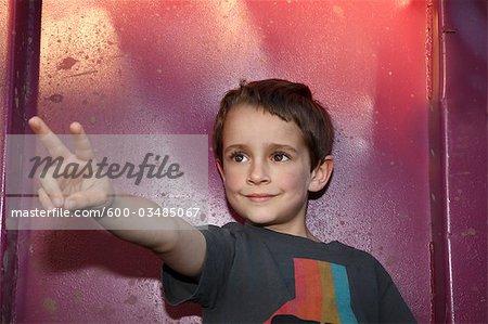 Portrait de garçon faisant le geste de la main
