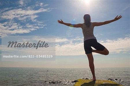 Rückansicht einer Frau praktizieren Yoga mit Blick auf das Meer