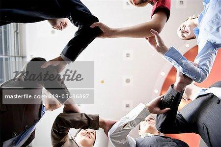 Geschäftsleute, die Hand in Hand im Kreis
