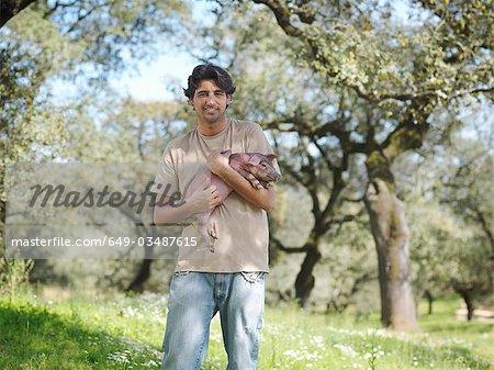 Homme tenant un porcelet champ de ferme