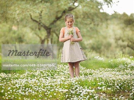 Enfant tenant un bouquet de marguerites