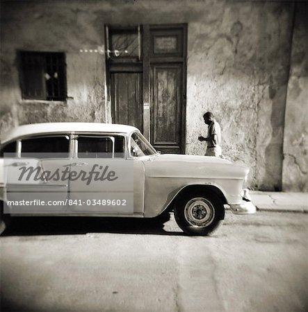 Image prise avec un Holga moyen format 120 film toy camera de l'homme en passant devant la vieille voiture américaine, la Havane, Cuba, Antilles, Amérique centrale