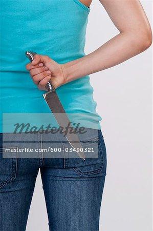 Femme tenant un couteau derrière son dos