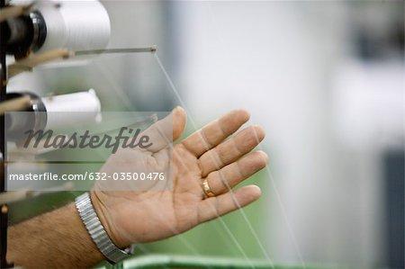 Vérifier la tension du fil sur métier à tisser en usine de tissage de machiniste