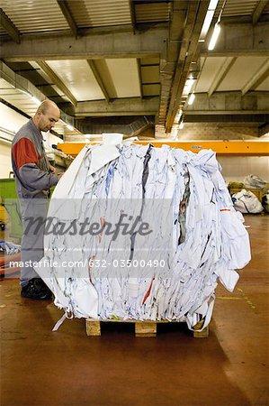 Machiniste écrit poids sur une botte de bâches PVC après avoir pesé il