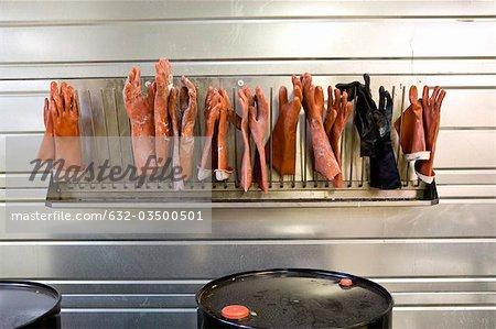 Tissu enduit plante, gants en caoutchouc sur la grille de séchage