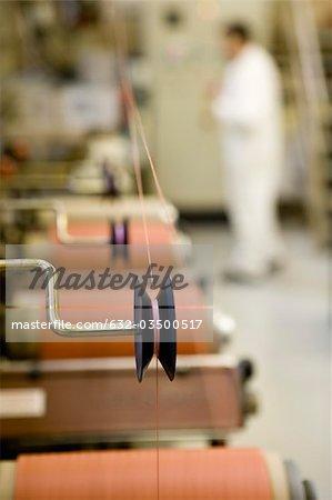 Département de fabrication textile composite recyclable d'usine, mécanicien travaillant sur la machine d'enduit de fil