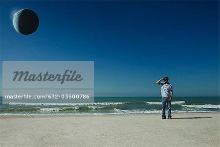 Homme sur la plage observant eclipse