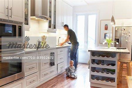 Laver la vaisselle avec bébé assis sur le plancher de l'homme