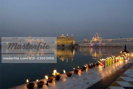 India, Punjab, Amritsar, the Golden Temple, lightning of candles by faithfuls during Guru Parab.